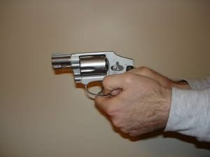Thumbs curled with the revolver